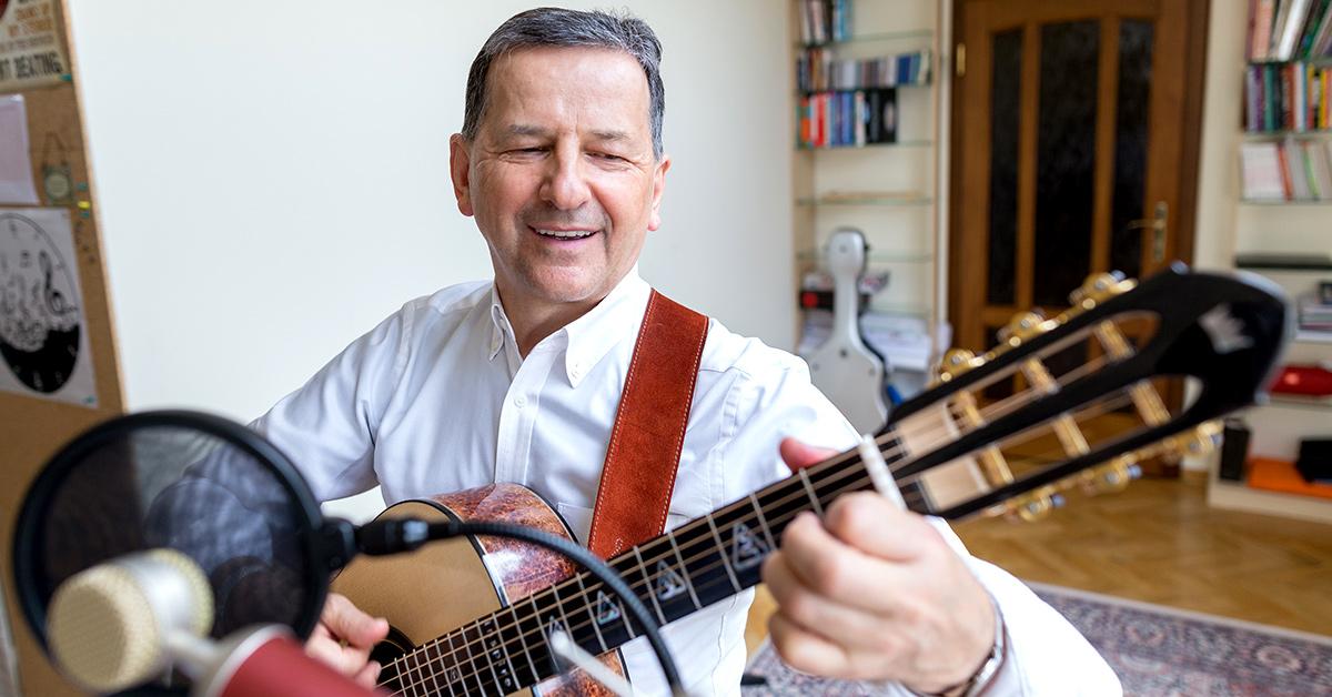 Zdzisław Dąbczyński gra na gitarze i śpiewa